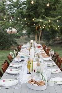 Long table set with plates and glasses, food and drink in a garden.